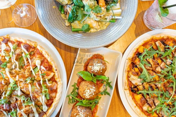 pizzas and arancini balls on a table at the deck restaurant, airlie beach