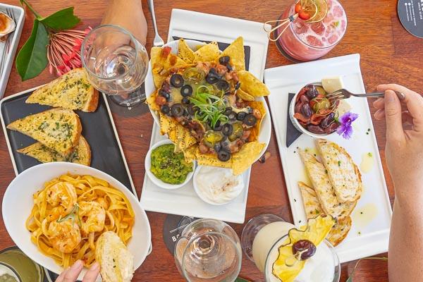 nachos, olives, pasta and various cocktails at bar at breeze bar, airlie beach, whitsundays