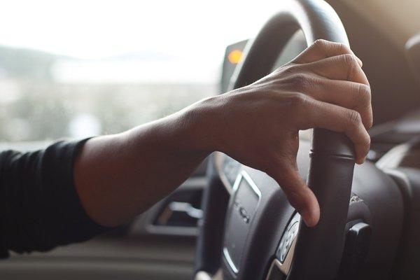 hand steering a car wheel